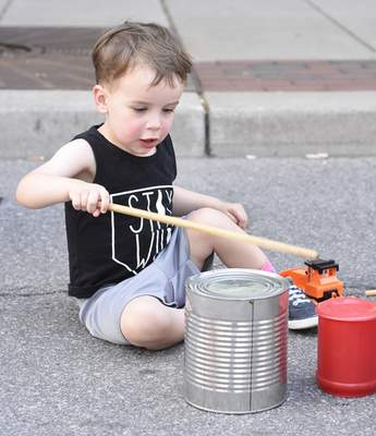 Wesley Radtke, 2, enjoys the drums/kid's area set out by the Dumpster Drummers during Buskerfest on Saturday.