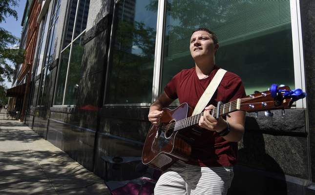 Rachel Von Stroup | The Journal Gazette  Gavin Rhinehart, 20, performs on the acoustic guitar during Buskerfest on Saturday June 29, 2019 in downtown Fort Wayne. BuskerFest is presented by the Downtown Improvement District, and is Downtown's celebration of the street performer and features a variety of local, regional and national acts. VIDEO