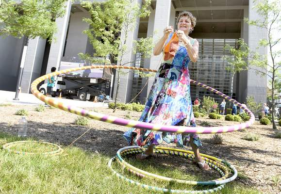 Rachel Von Stroup | The Journal Gazette Bonnie Manning knits a place mat while hula hooping during Buskerfest on Saturday outside the Indiana Michigan Power Center. For more on the event, turn to Page 4C.