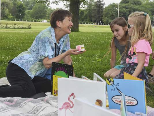 Michelle Davies | The Journal Gazette Allen County Public Library librarian Mary Voors shows a story cube Monday at Lawton Park to sisters Lucy Ambriole, 5, right, and Lola Ambriole, 9,  during Storytime in the Park.