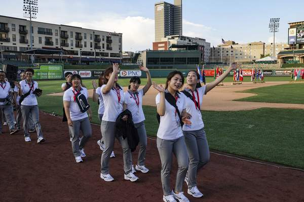 Team Korea waves to the crowd as it walks onto the field for the opening ceremony  Tuesday.