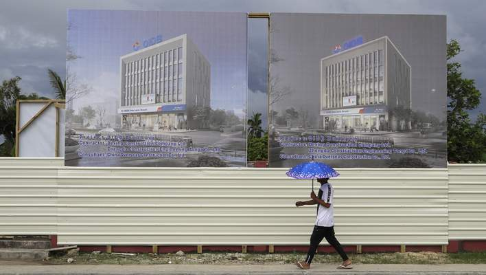 In this Wednesday, April 10, 2019, photo, a man walks past a development site for a Chinese Investment bank in Nuku'alofa, Tonga. (AP Photo/Mark Baker)