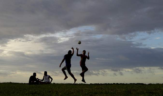 In this Wednesday, April 10, 2019, photo, young men play a game of rugby at sunset in Nuku'alofa, Tonga. (AP Photo/Mark Baker)