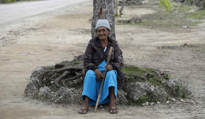 In this April 7, 2019, photo, a local woman sits under a tree in Nuku'alofa, Tonga. (AP Photo/Mark Baker)