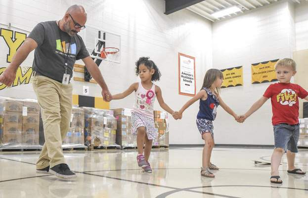 Michelle Davies | The Journal Gazette Haley Elementary School Principal Brian Howard helps incoming kindergarteners distinguish their left feet from their right during Kindergarten Countdown on Wednesday morning.