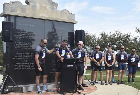 Michelle Davies | The Journal Gazette Kevin Getz of Indiana State Police is supported by fellow cyclists Ryan Skaggs, left,  and Bryant Orem  as he reads the memorial for fallen Trooper David Rich on Wednesday at the Law Enforcement/Firefighters Memorial on Wells Street.