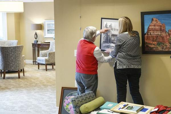 Mike Moore | The Journal Gazette Local artist Jerry Hertenstein, left and Exhibition Chairperson Nancy Longmate, right hang a painting in the Heritage Pointe Gallery for the May-June Exhibition taken on Tuesday 04.30.19
