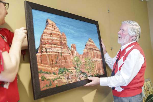 Mike Moore | The Journal Gazette Local artist Jerry Hertenstein hangs his painting in the Heritage Pointe Gallery for the May-June Exhibition taken on Tuesday 04.30.19