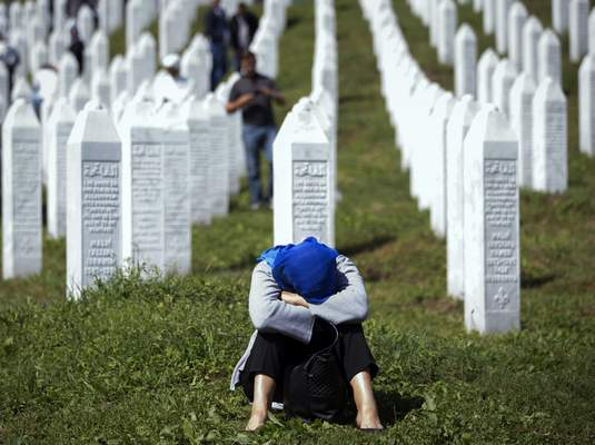 A woman rests at the memorial cemetery, prior to the funeral in Potocari, near Srebrenica, Bosnia, Thursday, July 11, 2019.  (AP Photo/Darko Bandic)