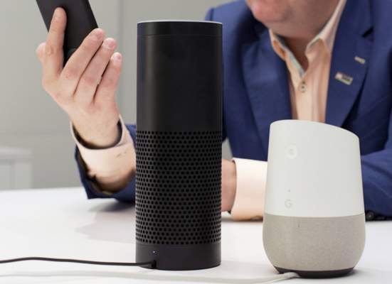 FILE - In this June 14, 2018, photo, an Amazon Echo, center, and a Google Home, right, are displayed in New York. (AP Photo/Mark Lennihan, File)