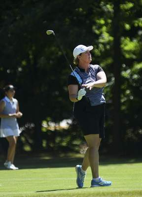 Katie Fyfe | The Journal Gazette Lori Stinson watches the flight of her ball on the 14 hole Friday during the first round of the Women's City Golf Tournament at Autumn Ridge.