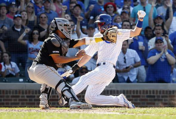 Associated Press The Cubs' Kris Bryant slides past Pirates catcher Elias Diaz to score the tiebreaking run in the eighth inning of Chicago's win Friday.
