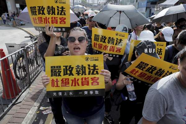 Protesters hold up words that read: Strict enforcing of law against smugglers of grey goods in Hong Kong Saturday, July 13, 2019. (AP Photo/Kin Cheung)