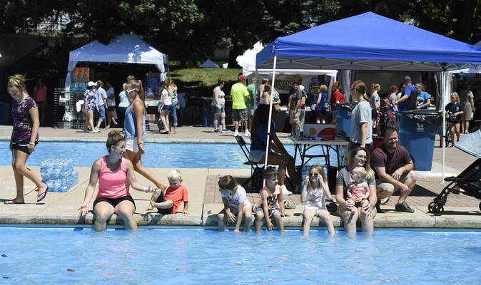 Rachel Von Stroup | The Journal Gazette  Families enjoy cooling down by the fountain during Art in the Park in Freimann Square on Saturday July 13, 2019. The two day juried fine art show continues today, Sunday from 11 a.m. - 5 p.m.