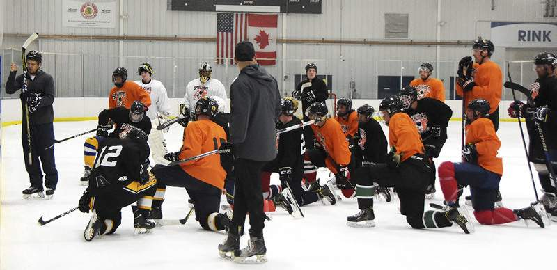 Katie Fyfe | The Journal Gazette Coach Lincoln Kaleigh Schrock, left, shows off a drill during tryouts for the new junior hockey team Saturday at SportONE Parkview Icehouse.