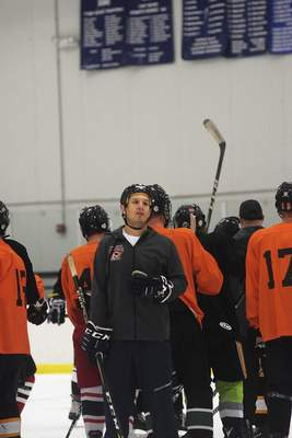 Katie Fyfe | The Journal Gazette Coach Lincoln Kaleigh Schrock watches players during tryouts for a new junior hockey team the Fort Wayne Spacemen at SportONE Parkview Icehouse on Saturday.