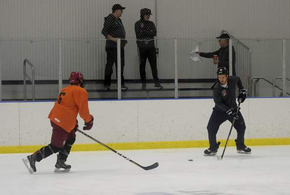Katie Fyfe | The Journal Gazette Coach Lincoln Kaleigh Schrock demonstrates a drill during tryouts for the Fort Wayne Spacemen at SportONE Parkview Icehouse on Saturday.