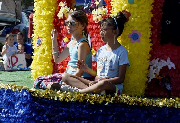 Girls ride on the Windsong Pictures float as it goes down Wayne Street during the parade Saturday morning.
