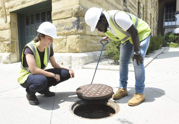 Rachel Von Stroup | The Journal Gazette City Utilities interns Maria Palmegiani and  Adama Samba inspect a manhole Tuesday in an alley off Barr Street next to the History Center in downtown Fort Wayne.