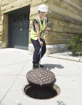 Rachel Von Stroup | The Journal Gazette  City Utilities Intern Maria Palmegiani works on opening up a manhole structure in an alley off of Barr St. next to the History Center in downtown Fort Wayne during work on Tuesday July 9, 2019.