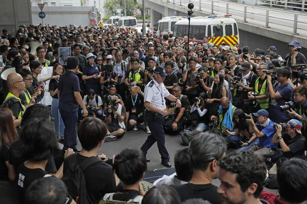 A police officer, center, received a letter as hundreds of journalists attend a silent march outside the police headquarters in Hong Kong, Sunday, July 14, 2019, demanding police to stop assaulting journalists and obstructing reporting. (AP Photo/Kin Cheung)