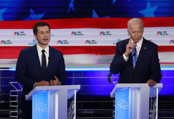 FILE - In this June 27, 2019, file photo, Democratic presidential candidate South Bend Mayor Pete Buttigieg, left, speaks as former vice president Joe Biden gestures during the Democratic primary debate hosted by NBC News at the Adrienne Arsht Center for the Performing Art in Miami. (AP Photo/Wilfredo Lee, File)