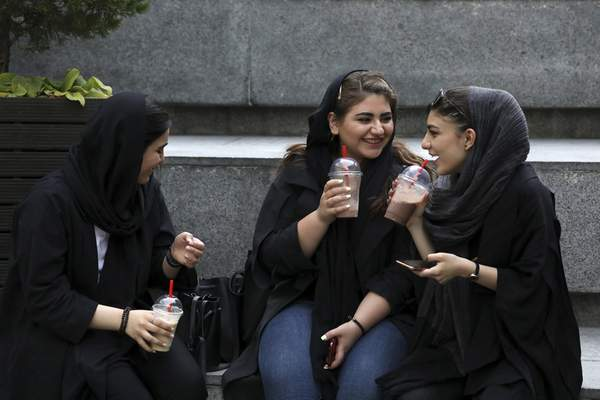 In this Tuesday, July 2, 2019 photo, youngsters spend an afternoon while siting on steps outside a shopping mall in northern Tehran, Iran. A few daring women in Iran's capital have been taking off their mandatory headscarves, or hijabs, in public, risking arrest and drawing the ire of hard-liners. (AP Photo/Vahid Salemi)