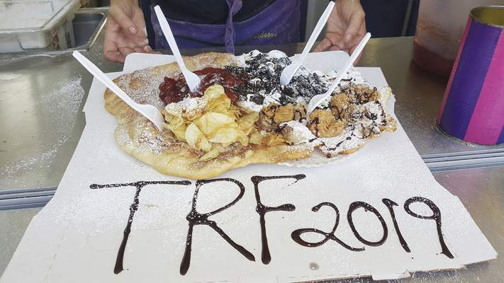 Photos by Ryan DuVall | The Journal Gazette The Willie Nelson giant elephant ear is topped with peanut butter sauce, peanut butter cups, strawberry topping, crumbled Oreos with buttercream and Lay's potato chips with caramel sauce at the Freak Show of Fried Oddities.