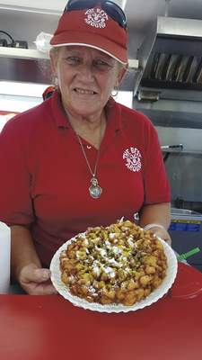 Carnival vending veteran Mama Jane Harris shows off her newest creation, the lemon-poppyseed funnel cake, at the Three Rivers Festival's Junk Food Alley.