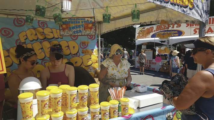 From left, Candace Luedeke of Decatur and Chelsea and LaTasha Laden of Fort Wayne work in the Wisconsin Fried Cheese shake-up stand at the Three Rivers Festival's Junk Food Alley.