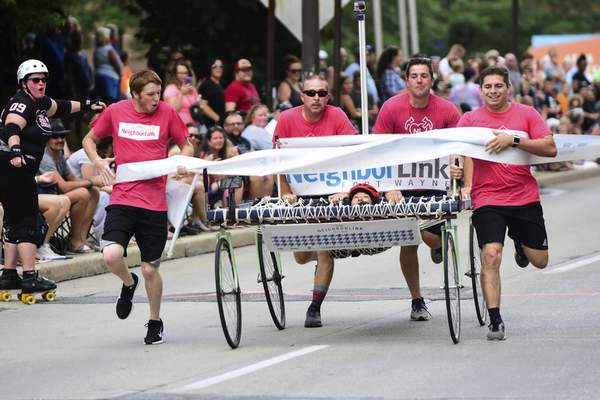 Mike Moore | The Journal Gazette Team Neighbor Link crosses the finish line while racing in the Three Rivers Festival Bed Race on Main Street downtown on Wednesday.