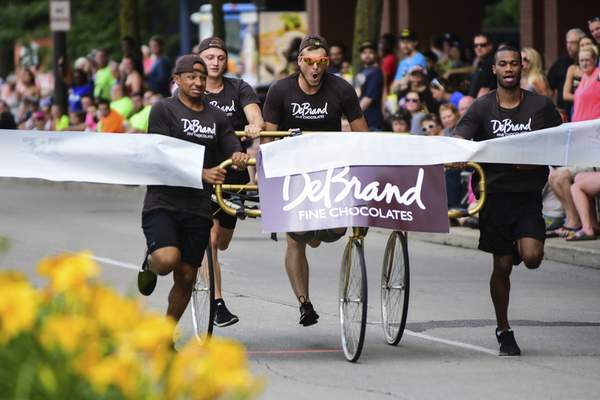 Mike Moore | The Journal Gazette Team DeBrand Fine Chocolates crosses the finish line while racing in the Three Rivers Festival Bed Race on Main Street downtown on Wednesday.