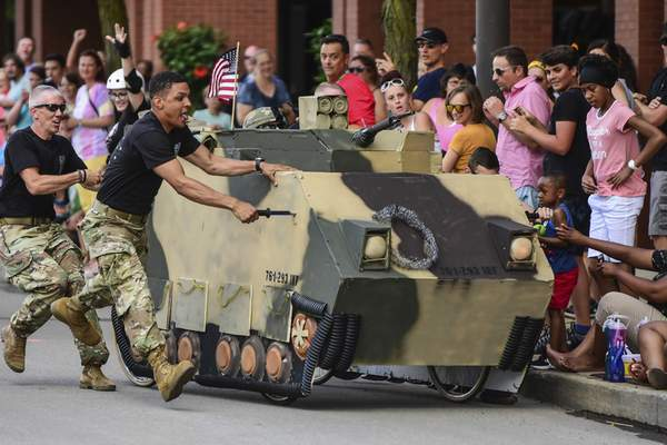 Mike Moore | The Journal Gazette The Army National Guard race team stops their bed-racer before striking the curb near spectators while racing in the Three Rivers Festival Bed Race on Main Street downtown on Wednesday.