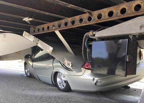 In this photo released Tuesday, July 16, 2019 by the Uxbridge Fire Department on its Facebook page, a car sits wedged under a tractor-trailer on Route 146 in Uxbridge, Mass. (Uxbridge Fire Department via AP)