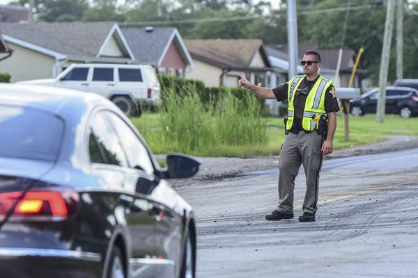 An Allen County sheriff's deputy directs traffic on Cook Road on Wednesday as construction crews repave Coldwater Road. (Photos by Mike Moore | The Journal Gazette)