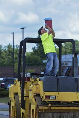 Wayne Asphalt heavy-equipment operator Denny Buesching demonstrates how he beats the heat while taking a break from paving Westfield Drive on Wednesday.