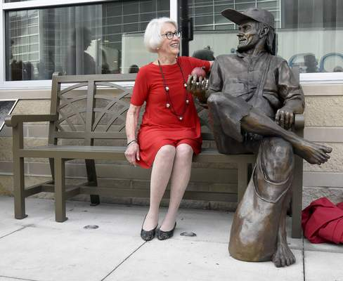 Nancy Stewart, chair of the Fort Wayne Public Art Commission, sits next to a new statue of Johnny Appleseed, which was unveiled Thursday, in front of the Hampton Inn & Suites.