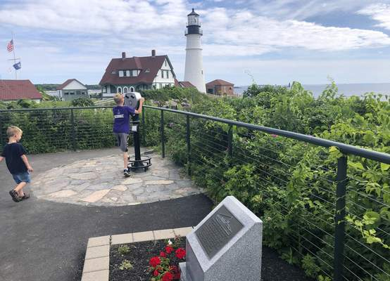 Children take in the view at Fort Williams Park at Cape Elizabeth, Maine, on Thursday, July 18, 2019, where a plaque, foreground, remembers those killed when the USS Eagle PE-56 was sunk During World War II off the Maine coast on April 23, 1945. (AP Photo/David Sharp)