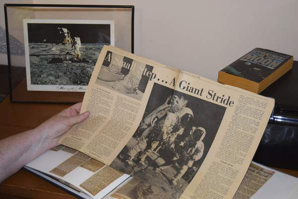 This 2019 photo provided by Cathy Goff shows her with newspaper clippings about the Apollo 11 moon landing mission at her home in King, N.C. (Courtesy Cathy Goff via AP)