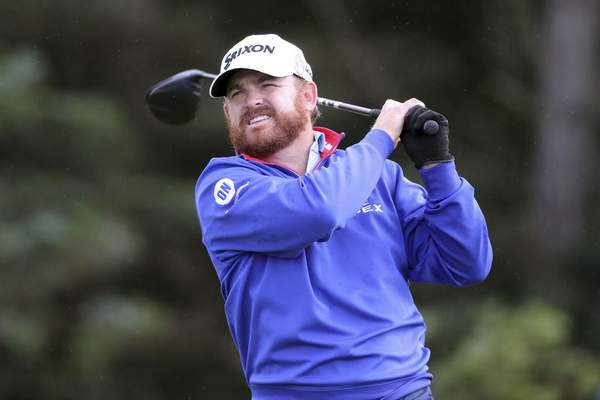 J.B. Holmes of Kentucky shot a 5-under 66 on Thursday to hold the early lead at the British Open.
