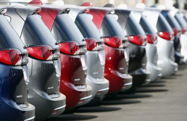 FILE - In this April 15, 2018 file photo, unsold 2018 Pacifica minivans sit on a Chrysler dealer's lot in the south Denver suburb of Englewood, Colo. Americans are being presented with two starkly different and inaccurate accounts of the state of the auto industry, one from President Donald Trump and the other from Democratic presidential candidate Kamala Harris. (AP Photo/David Zalubowski)