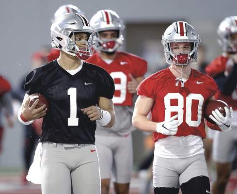 Associated Press Ohio State quarterback Justin Fields, left, and receiver K.J. Hill run through a drill in March. Fields, a transfer from Georgia, is the presumed starter.