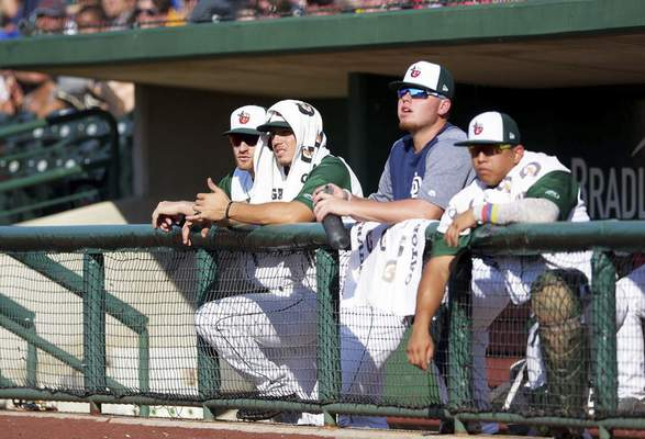 Katie Fyfe | The Journal Gazette TinCaps players try to stay cool in the dug out on a hot day during the game against the Cedar Rapids Kernels at Parkview Field on Saturday.