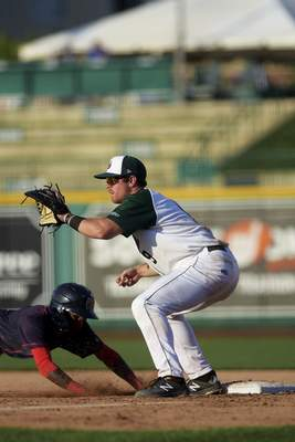 Katie Fyfe | The Journal Gazette TinCaps' Luke Becker goes to catch the ball while the Cedar Rapids Kernels' Daniel Ozoria slides back into first base at Parkview Field on Saturday.