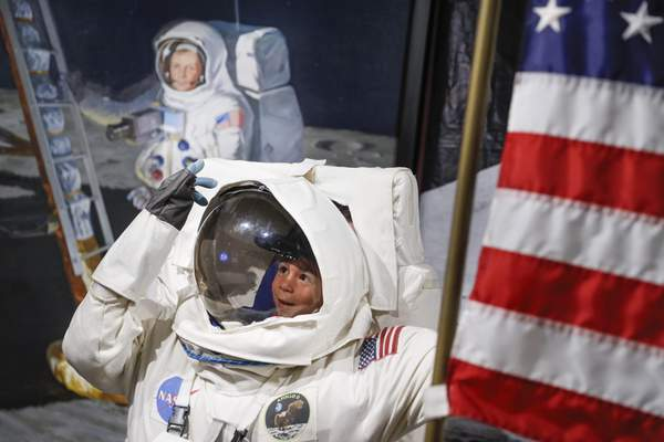 Associated Press A visitorposes fora photo beside a portrait of Neil Armstrong, the first man to walk on the moon, at the Armstrong Air and Space Museum on Saturday in Wapakoneta, Ohio.