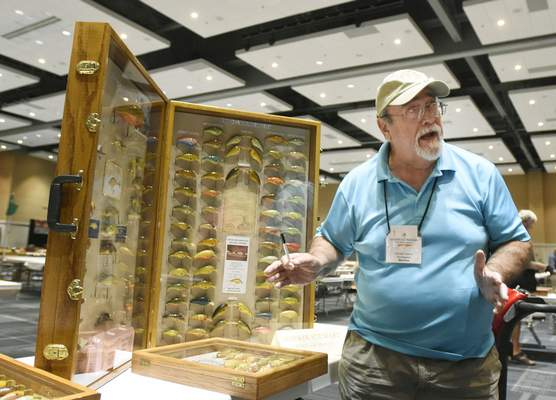 Darwin Stewart of Clarksville, Tenn., displays his Big O lures, handcrafted by Fred Young, Saturday at the  National Fishing Lure Collectors Club show. Stewart says the lures are made of balsa wood and designed for bass fishing.