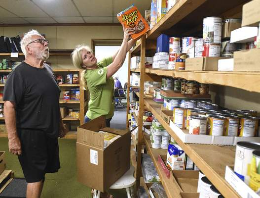 Michelle Davies   The Journal Gazette Tom Humbrecht, left, and Stacey Ruiz organize donations on the shelves at St. Patrick's Catholic Church food pantry.