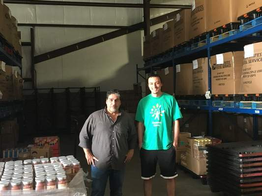Dylan Sinn   The Journal Gazette Chris Alvarez, left, the warehouse manager at Associated Churches food bank, and warehouse assistant Kyle Pelz sort, box and deliver food to 25 local food pantries.