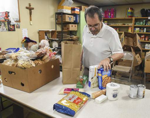 Michelle Davies   The Journal Gazette Jim Laughlin, a volunteer at St. Patrick's Catholic Church food bank for 10 years, packs a bag of supplies.