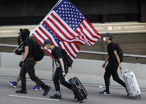 Protesters carry United States flags, during a march in Hong Kong, Sunday, July 21, 2019. (AP Photo/Vincent Yu)